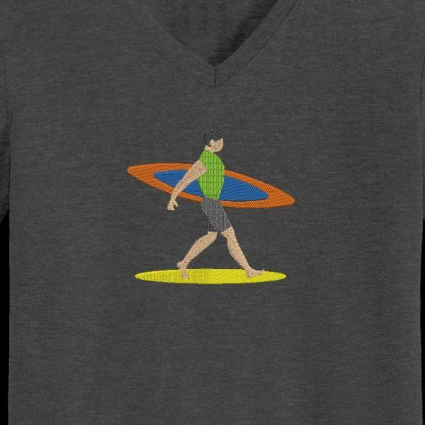 Motif de broderie machine d'un surfeur qui marche sur une plage de sable avec sa planche de surf sous le bras