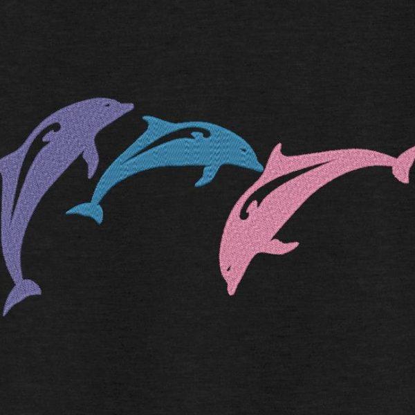 Motif de broderie machine trio de dauphins qui font des sauts dans l'océan.